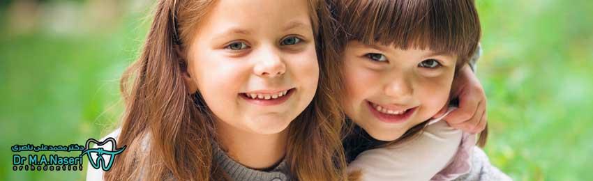 دو دختر بچه با لبخند و دندان های ارتودنسی